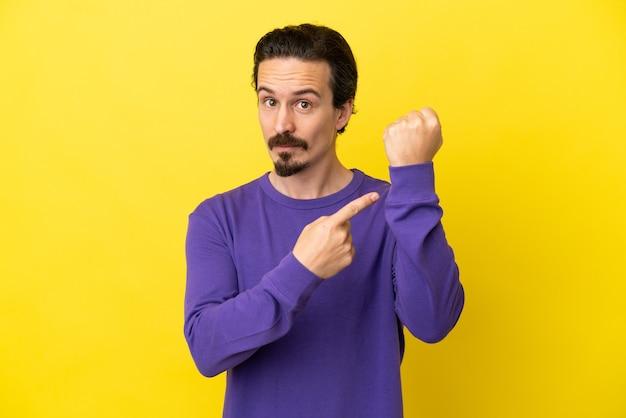 Giovane uomo caucasico isolato su sfondo giallo che fa il gesto di essere in ritardo