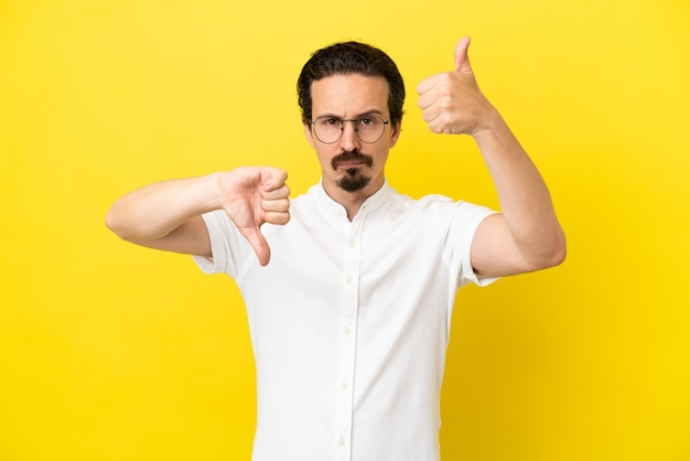 Giovane uomo caucasico isolato su sfondo giallo facendo segno buono-cattivo. indeciso tra si o no
