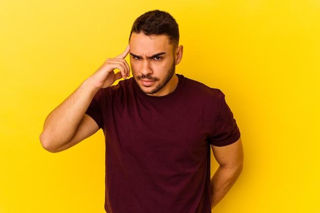 Giovane uomo caucasico isolato su sfondo giallo che punta il tempio con il dito, pensando, concentrato su un compito.