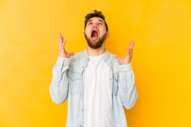 Giovane uomo caucasico isolato su sfondo giallo che grida al cielo, alzando lo sguardo, frustrato.