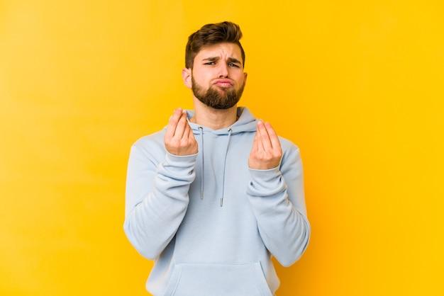 Giovane uomo caucasico isolato su sfondo giallo che mostra che non ha soldi.
