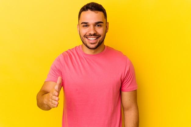 Giovane uomo caucasico isolato su sfondo giallo che allunga la mano alla telecamera in gesto di saluto.
