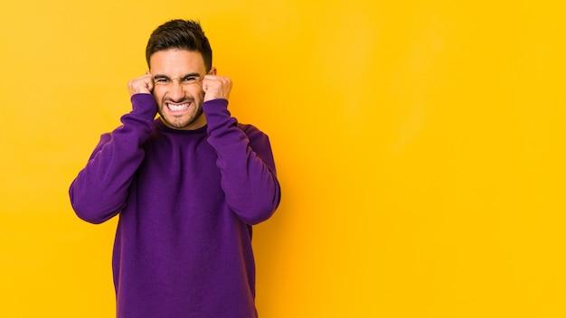Giovane uomo caucasico isolato su bakground giallo che copre le orecchie con le mani. Foto Premium