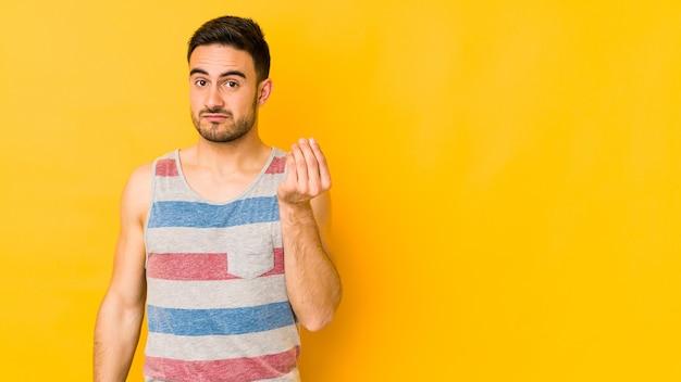 Giovane uomo caucasico isolato su bakground giallo che mostra che non ha soldi.