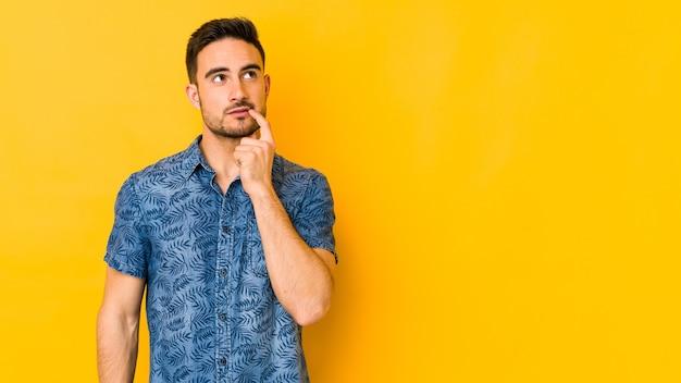 Giovane uomo caucasico isolato su giallo che guarda lateralmente con espressione dubbiosa e scettica.
