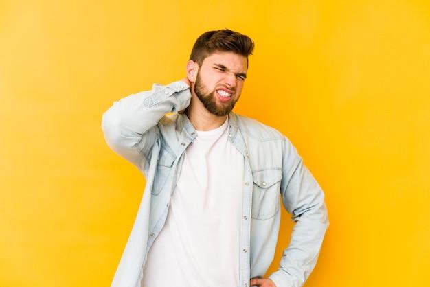 Giovane uomo caucasico isolato su giallo che soffre di dolore al collo a causa di uno stile di vita sedentario.