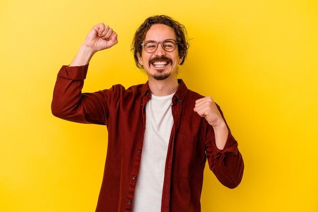 Giovane uomo caucasico isolato sulla parete gialla ballando e divertendosi