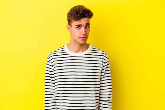 Giovane uomo caucasico isolato sul muro giallo faccia triste e seria, sentendosi infelice e scontento