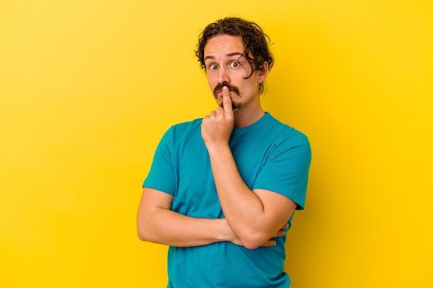 Giovane uomo caucasico isolato sulla parete gialla infelice guardando davanti con espressione sarcastica