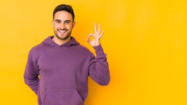 Il giovane uomo caucasico isolato su giallo strizza l'occhio e tiene un gesto giusto con la mano.