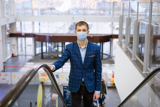 Giovane uomo caucasico in una giacca e una mascherina medica si arrampica sulla scala mobile in un centro commerciale