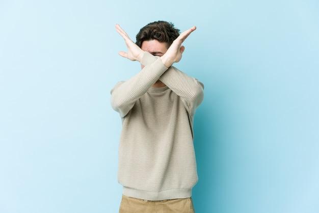 Giovane uomo caucasico mantenendo due braccia incrociate, concetto di negazione.