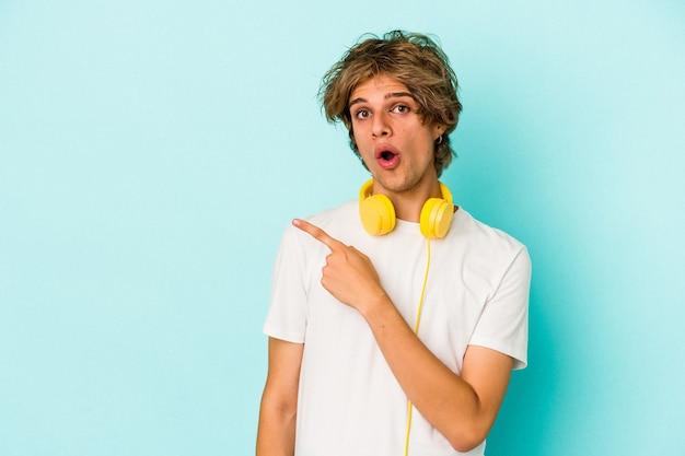 Giovane uomo caucasico che ascolta musica isolato su sfondo blu che punta al lato