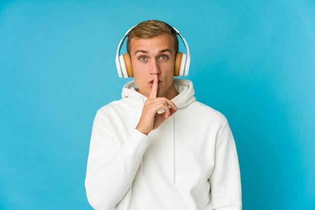 Musica d'ascolto del giovane uomo caucasico isolata sull'azzurro che mantiene un segreto o che chiede il silenzio.