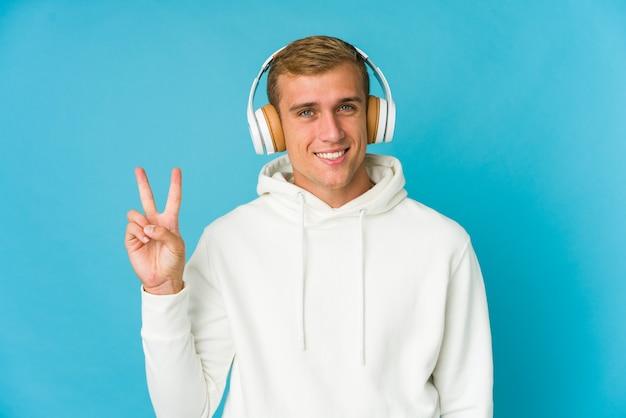 Musica d'ascolto del giovane uomo caucasico isolata sull'azzurro che mostra il numero due con le dita.