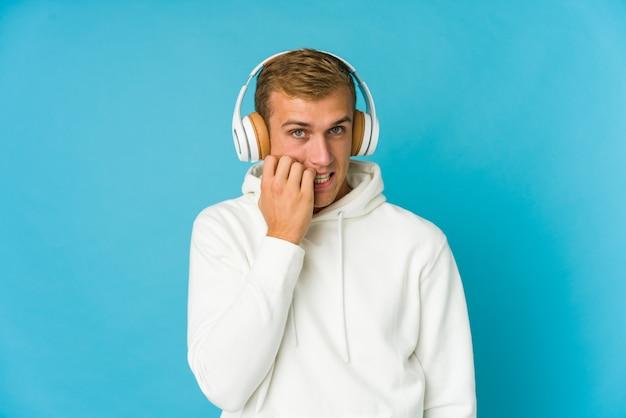 Musica d'ascolto del giovane uomo caucasico isolata sulla parete blu confusa, si sente dubbioso e insicuro.