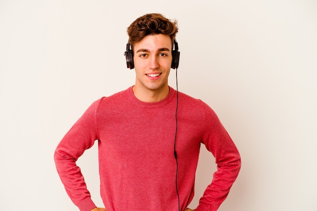 Giovane uomo caucasico ascoltando musica isolata su sfondo bianco fiducioso mantenendo le mani sui fianchi.