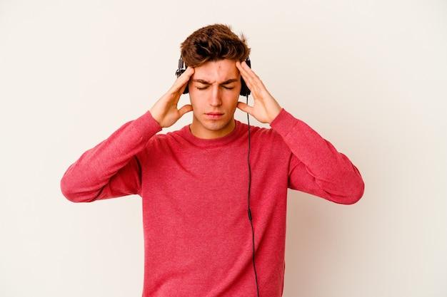 Giovane uomo caucasico che ascolta musica isolato su sfondo bianco toccando le tempie e avendo mal di testa.