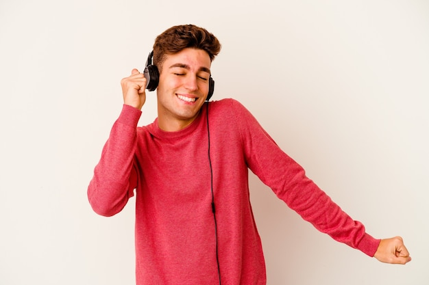 Giovane uomo caucasico che ascolta la musica isolata sulla parete bianca ballando e divertendosi.