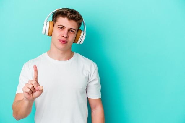 Giovane uomo caucasico che ascolta musica con le cuffie isolate su sfondo blu che mostra il numero uno con il dito.