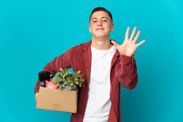 Giovane uomo caucasico che fa una mossa mentre prende in mano una scatola piena di cose isolate su blu contando cinque con le dita