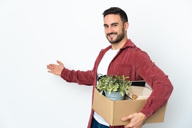 Giovane uomo caucasico che fa una mossa mentre prende in mano una scatola piena di cose isolate sul muro bianco che estende le mani di lato per invitare a venire