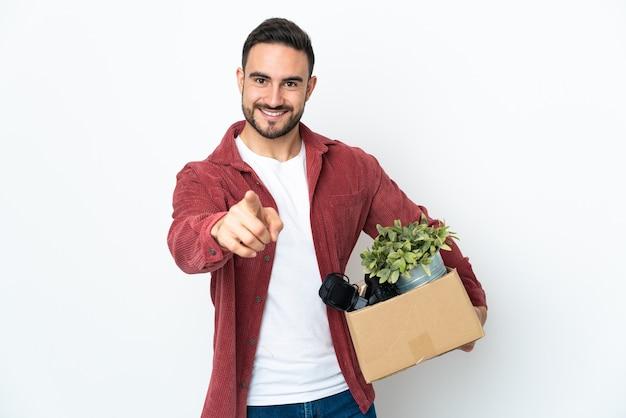 Giovane uomo caucasico che fa una mossa mentre prende in mano una scatola piena di cose isolate sul muro bianco che punta davanti con espressione felice