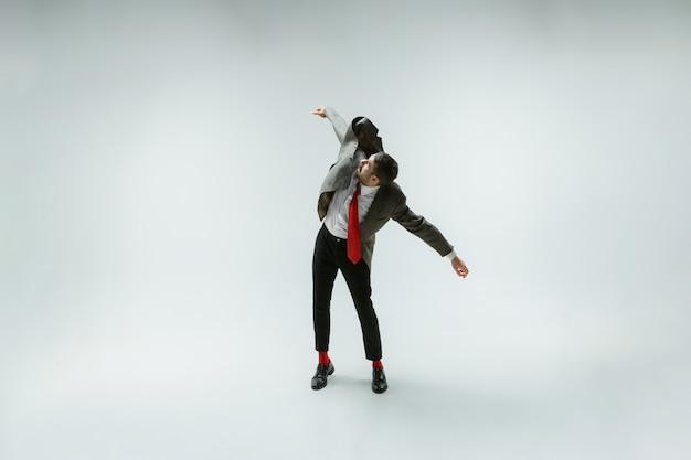 Giovane uomo caucasico in movimento flessibile sulla parete bianca