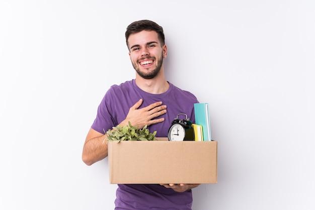 Il giovane uomo caucasico che trasloca una nuova casa isolata ride ad alta voce mantenendo la mano sul petto.
