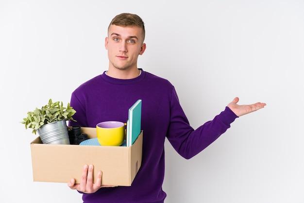Giovane uomo caucasico che si trasferisce in una nuova casa che mostra uno spazio di copia su un palmo e che tiene un'altra mano sulla vita.