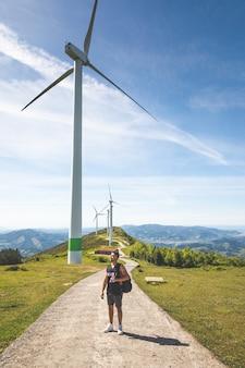 Giovane uomo caucasico vicino ai mulini a vento in cima alla montagna di oiz; paesi baschi.
