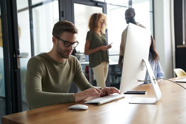 Giovane impiegato di ufficio caucasico che scrive qualcosa sul computer mentre è seduto al suo posto di lavoro in