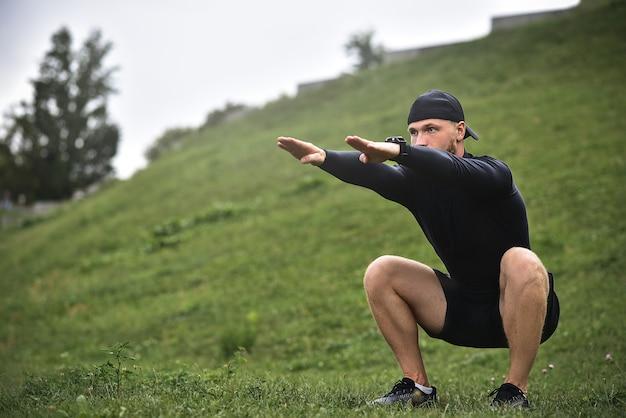 Giovane uomo caucasico che esegue squat prima di fare jogging sul sentiero nel parco.