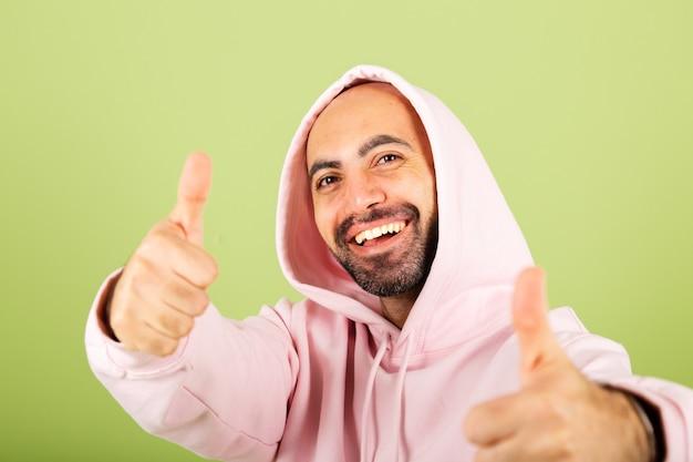 Il giovane uomo caucasico in felpa con cappuccio rosa isolato, felice che fa il successo di gesto eccitato mostra i pollici in su