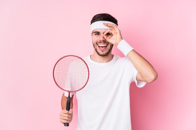 Il giovane uomo caucasico che gioca a badminton ha isolato eccitato mantenendo il gesto giusto sull'occhio.