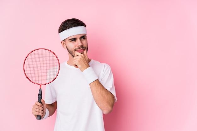 Giovane uomo caucasico che gioca a badminton isolato guardando lateralmente con espressione dubbiosa e scettica.