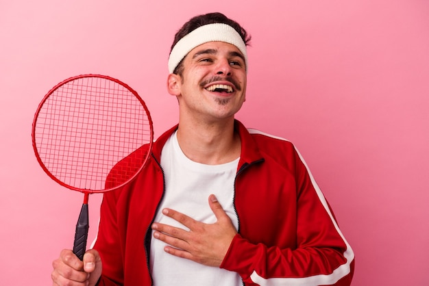 Il giovane uomo caucasico che gioca a badminton isolato su sfondo rosa ride forte tenendo la mano sul petto.