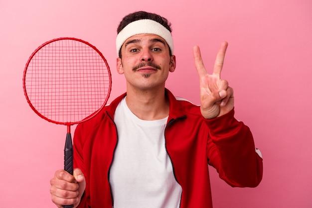 Giovane uomo caucasico che gioca a badminton isolato su sfondo rosa che mostra il numero due con le dita.