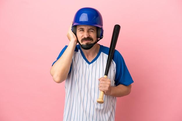 Giovane uomo caucasico che gioca a baseball isolato su sfondo rosa frustrato e che copre le orecchie