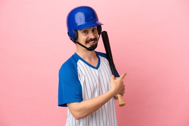 Giovane uomo caucasico che gioca a baseball isolato su sfondo rosa che punta indietro