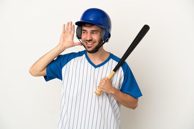 Giovane uomo caucasico che gioca a baseball isolato su sfondo bianco ascoltando qualcosa mettendo la mano sull'orecchio