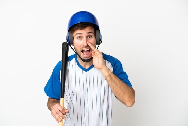 Giovane uomo caucasico che gioca a baseball isolato su sfondo bianco che grida con la bocca spalancata