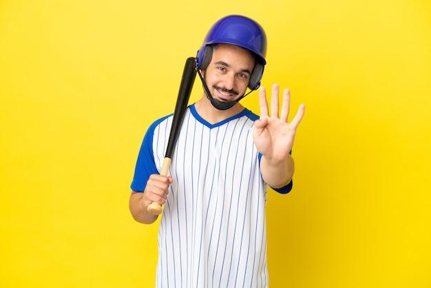 Giovane uomo caucasico che gioca a baseball isolato su sfondo giallo felice e conta quattro con le dita