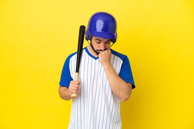 Giovane uomo caucasico che gioca a baseball isolato su sfondo giallo avendo dubbi