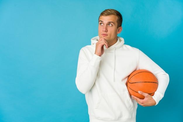 Giovane uomo caucasico che gioca a basket isolato su blu guardando lateralmente con espressione dubbiosa e scettica.