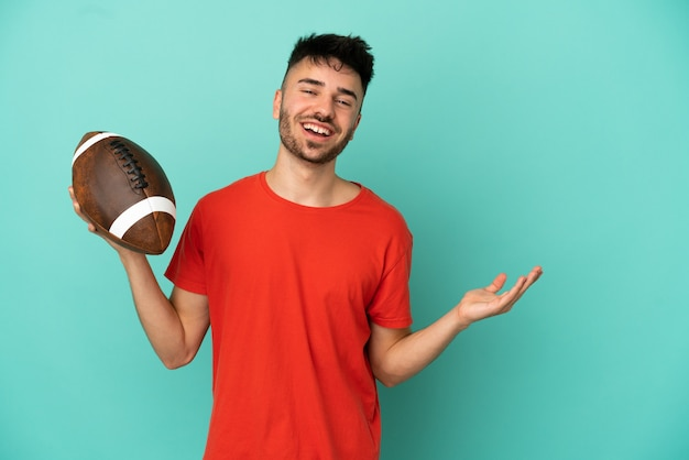 Giovane uomo caucasico che gioca a rugby isolato su sfondo blu estendendo le mani di lato per invitare a venire