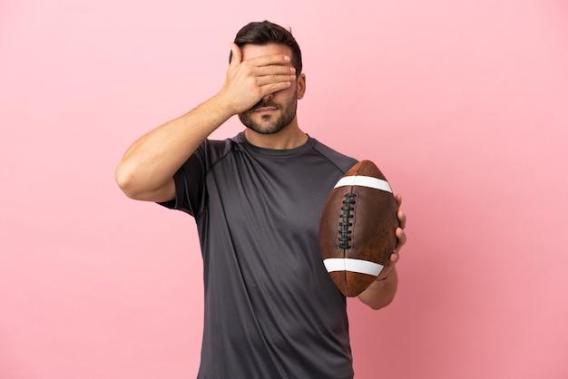 Giovane uomo caucasico che gioca a rugby isolato su sfondo rosa che copre gli occhi con le mani. non voglio vedere qualcosa
