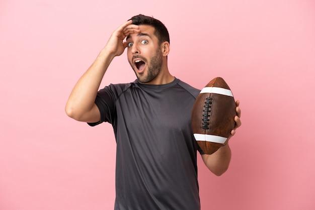 Giovane uomo caucasico che gioca a rugby isolato su sfondo rosa facendo un gesto a sorpresa mentre guarda di lato
