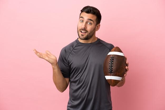 Giovane uomo caucasico che gioca a rugby isolato su sfondo rosa allungando le mani di lato per invitare a venire