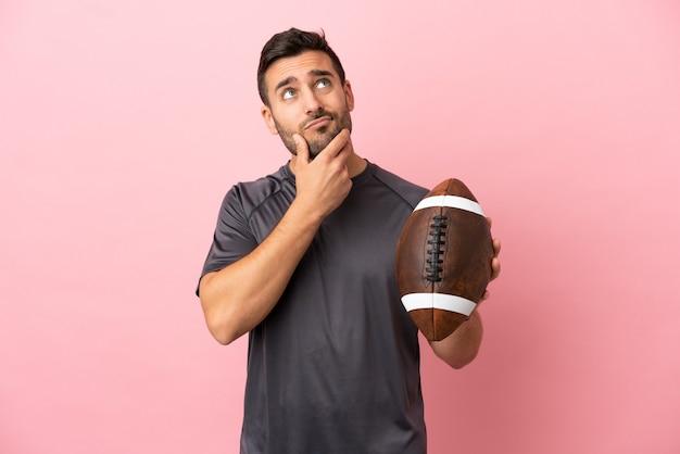 Giovane uomo caucasico che gioca a rugby isolato su sfondo rosa avendo dubbi